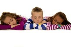 Tres niños que colocan los pijamas del invierno que llevan dormidos Foto de archivo