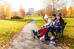 Tres niños que consiguen listos para patinar Foto de archivo libre de regalías