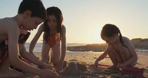 Tres niños que construyen la arena se escudan en la playa durante puesta del sol almacen de metraje de vídeo