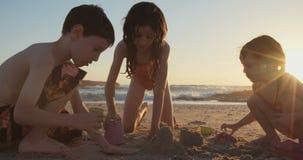 Tres niños que construyen la arena se escudan en la playa durante puesta del sol metrajes