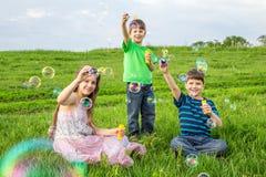 Tres niños que explotan las burbujas de jabón en césped Fotos de archivo libres de regalías