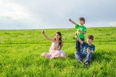 Tres niños que explotan las burbujas de jabón en césped soleado Fotografía de archivo