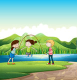 Tres niños que juegan cerca del río Imagenes de archivo