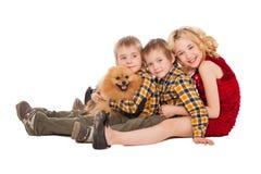 Tres niños que juegan con el pequeño perro que se sienta en el backgrou blanco imágenes de archivo libres de regalías