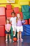 Tres niños que juegan a fútbol en gimnasio Imagenes de archivo