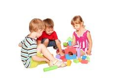 Tres niños que juegan y que construyen junto. Foto de archivo