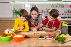 Tres niños que leen al cocinero reservan, haciendo la cena Foto de archivo libre de regalías