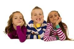 Tres niños que llevan los pijamas de la Navidad con su barbilla en las manos Imágenes de archivo libres de regalías