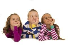 Tres niños que llevan los pijamas del invierno que miran para arriba sonrientes Fotos de archivo libres de regalías