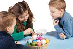 Tres niños que pintan los huevos de Pascua imagen de archivo