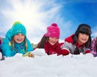 Tres niños que ponen en nieve Fotos de archivo libres de regalías