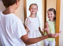 Tres niños que se colocan en la entrada de la casa Fotografía de archivo