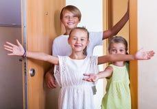 Tres niños que se colocan en la entrada de la casa Imagen de archivo