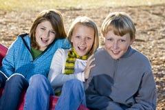 Tres niños que se sientan en diapositiva Imagenes de archivo