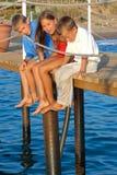 Tres niños que se sientan en el embarcadero. Imagenes de archivo