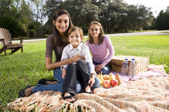 Tres niños que se sientan en la manta de la comida campestre en parque Imágenes de archivo libres de regalías