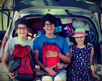 Tres niños que se sientan en un coche antes de ir el día de fiesta fotografía de archivo libre de regalías