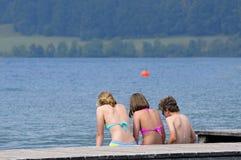 Tres niños que se sientan en un embarcadero por el lago Foto de archivo