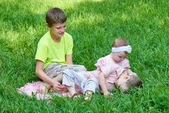 Tres niños se sientan en hierba, jugando y divirtiéndose Foto de archivo