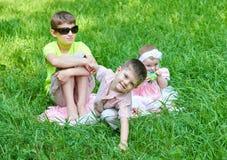 Tres niños se sientan en hierba, jugando y divirtiéndose Fotografía de archivo libre de regalías