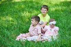 Tres niños se sientan en hierba, jugando y divirtiéndose Fotos de archivo libres de regalías