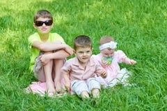 Tres niños se sientan en hierba, jugando y divirtiéndose Imágenes de archivo libres de regalías
