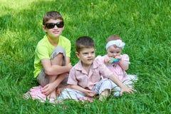 Tres niños se sientan en hierba, jugando y divirtiéndose Imagen de archivo libre de regalías
