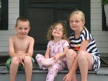 Tres niños sonrientes en el pórche de entrada Fotos de archivo libres de regalías