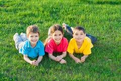 Tres niños sonrientes en el prado foto de archivo libre de regalías