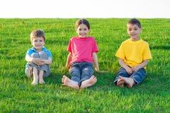Tres niños sonrientes en el prado fotografía de archivo