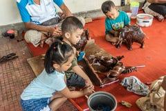 Tres ni?os trabajan en el negocio de Sari Pertiwi Wood Carving, Juga, Bali, Indonesia imagen de archivo libre de regalías