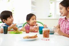 Tres niños asiáticos que desayunan junto en cocina Imagenes de archivo