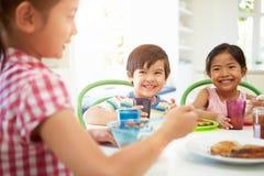 Tres niños asiáticos que desayunan junto en cocina Foto de archivo libre de regalías