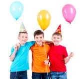 Tres niños pequeños con los globos y el sombrero coloreados del partido Imagen de archivo libre de regalías