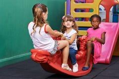 Tres niños que oscilan en eje de balancín Imagen de archivo libre de regalías