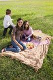 Tres niños que tienen una comida campestre en el parque Fotos de archivo