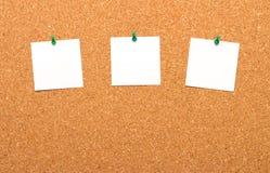 Tres notas fijadas en tablero del corcho Foto de archivo libre de regalías