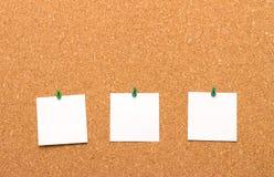 Tres notas fijadas a un tablero del corcho Fotografía de archivo libre de regalías