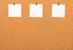 Tres notas fijadas a un tablero del corcho Fotos de archivo libres de regalías