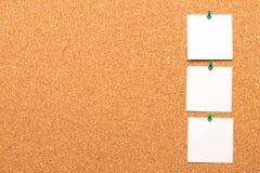 Tres notas fijadas a un tablero del corcho Foto de archivo