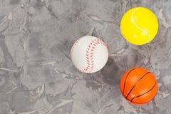 Tres nuevas bolas de goma suaves del baloncesto y del tenis y del béisbol en la forma de triángulo en el cemento gastado viejo imagenes de archivo