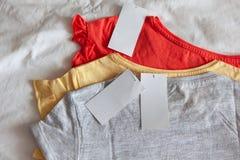 Tres nuevos niños o la camiseta de las mujeres, colores grises, rojos, amarillos, con la etiqueta limpia en el fondo blanco E foto de archivo