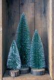 Tres objetos del árbol de navidad en una caja de madera fotos de archivo