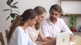 Tres oficinistas que planean el trabajo junto usando programa en línea del ordenador portátil almacen de metraje de vídeo