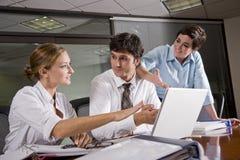 Tres oficinistas que se encuentran en la sala de reunión Fotos de archivo libres de regalías