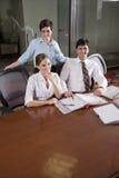 Tres oficinistas que trabajan en la sala de reunión Imagen de archivo libre de regalías