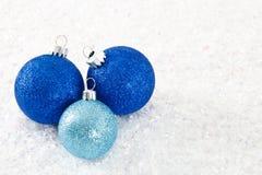 Tres ornamentos Glittery azules en el fondo Nevado Fotos de archivo libres de regalías