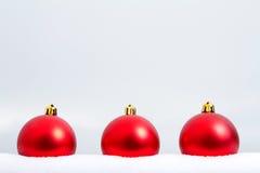 Tres ornamentos rojos de la Navidad en la nieve Imagen de archivo libre de regalías