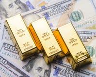Tres oros con los nuevos billetes de dólar del americano ciento Fotografía de archivo