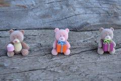 Tres osos del juguete con los regalos en el tablero fotos de archivo